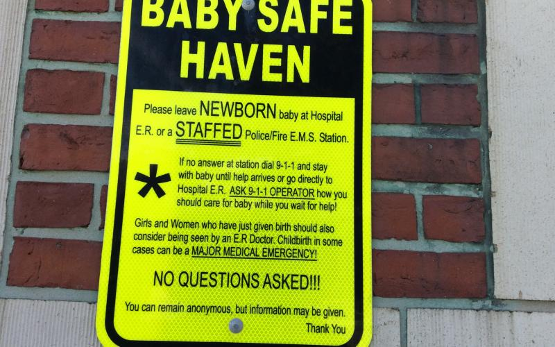 "Close-up of ""Baby Safe Haven"" sign on Inman Square Fire Station."