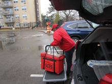 Doresta McIntosh getting bags of pre-packed meals out of her car.